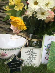 Visual Description:  thank you gifts from campers and SSPs to Brenda. Large white fruit bowl with pink flower engraved Silver star box, flower bouquet, plate with quote from Helen Keller, cards. The best and most beautiful things in the world can not be seen or touched but must be felt with the heart.