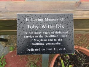 "Visual Description: The plaque reads ""In loving memory of Toby White-Dix for her many years of dedicated service to the DeafBlind Camp of Maryland and to the DeafBlind Community."""