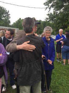 Visual Description: Ray Dix and Carol Cotton hug each other